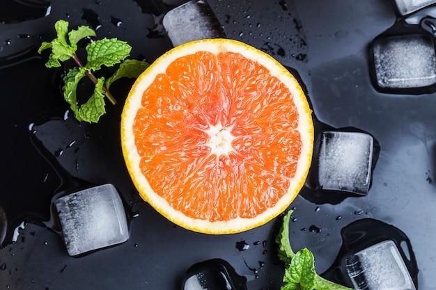 Vista dall'alto di mezza arancia con ghiaccio e menta