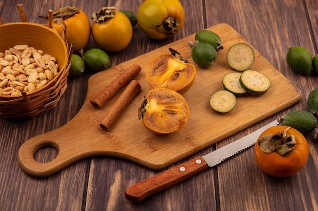 Vista dall'alto di metà frutti di cachi con fette di feijoas con bastoncini di cannella su una tavola da cucina in legno con arachidi su un secchio su uno sfondo di legno