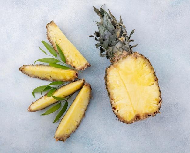 Vista superiore della metà delle fette di ananas e ananas sulla superficie bianca
