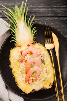 Top view half of pineapple with shrimps and golden cutlery