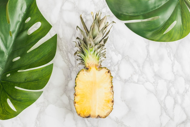 Top view half pineapple with tropical leaves