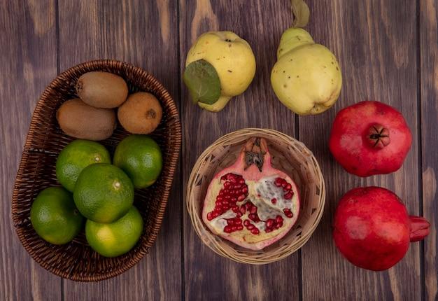 Merce nel cestino del melograno di vista superiore con i mandarini e le pere del kiwi sulla parete di legno