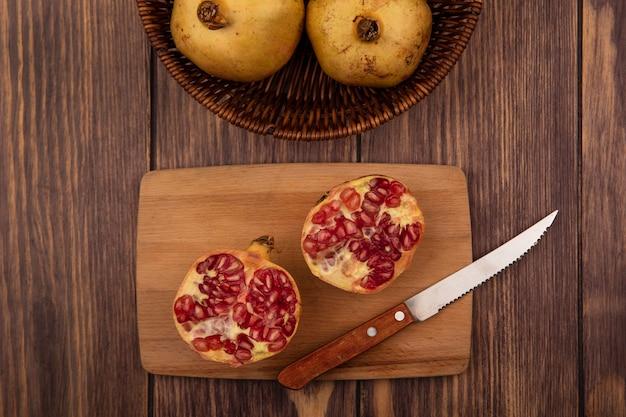 Vista dall'alto di mezze melograne su una tavola da cucina in legno con coltello con melograni su un secchio su una parete in legno