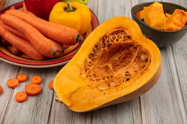 Top view of half pumpkin with colorful bell peppers on a plate with carrots with pumpkin slices on a bowl with chopped carrots isolated on a grey wooden background