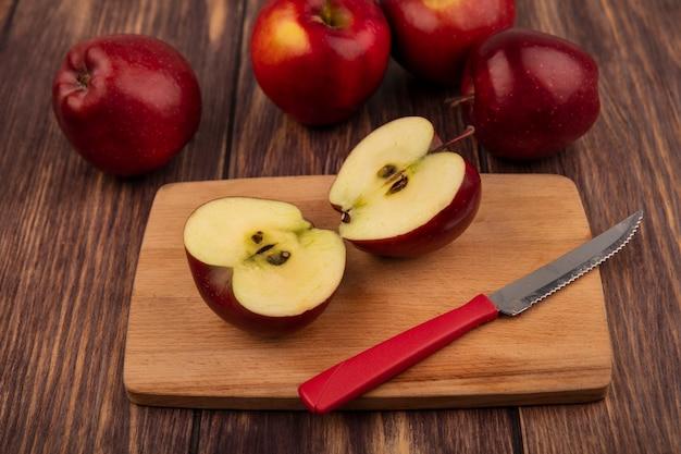 Vista dall'alto di mezze mele rosse su una tavola da cucina in legno con coltello con mele isolate su uno sfondo di legno