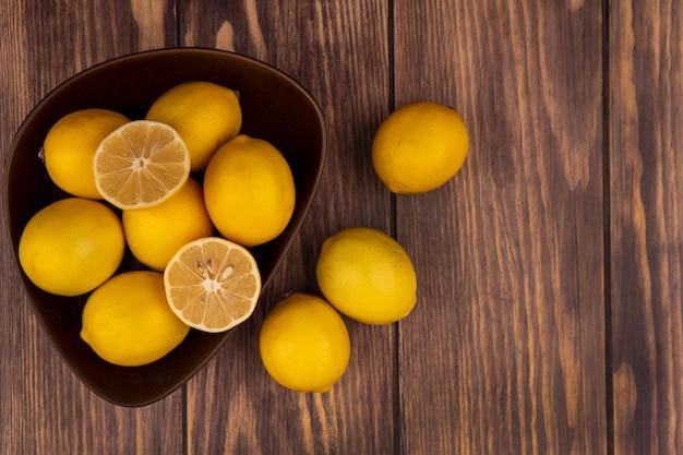 Vista dall'alto di metà e interi limoni su una ciotola con limoni isolati su una superficie in legno con spazio di copia
