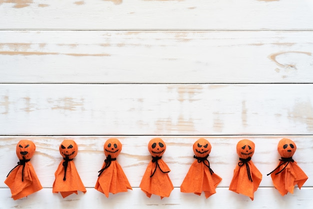 Top view of halloween crafts, orange paper ghost on white wooden background