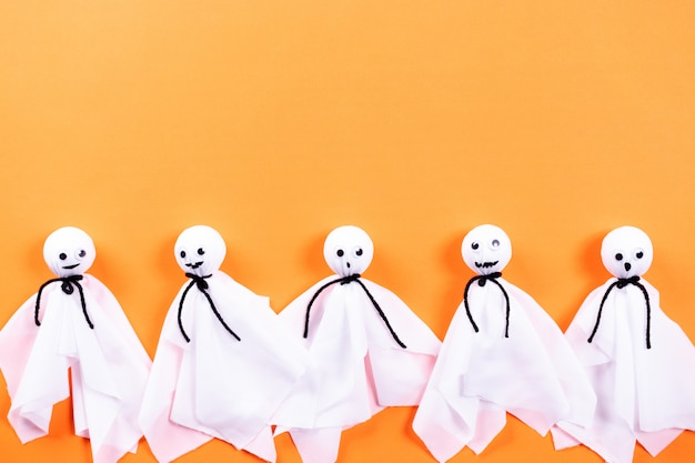 Top view of halloween crafts, paper ghost on orange paper background with copyspace