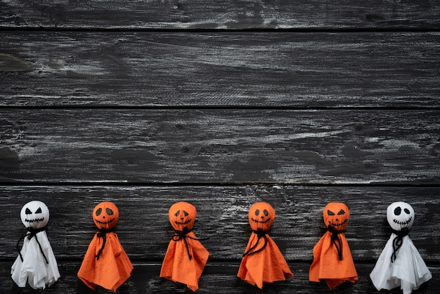 Top view of halloween crafts, white and orange paper ghost on black and white wooden backg