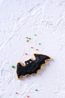 Top view of halloween festive decorated icing gingerbread sugar cookies on white background with copy space and flat lay layout.