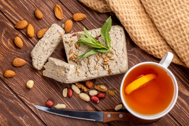 Top view halva from seeds with seeds with peanuts almonds a knife with a cup of tea with a slice of lemon