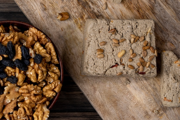 Top view of halva with sunflower seeds and walnuts in a bowl on a wooden board
