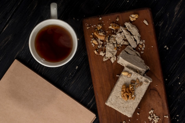 Top view of halva with sunflower seeds and walnuts on a wooden board and a cup of tea on rustic