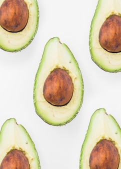 Top view of halved avocados on white background