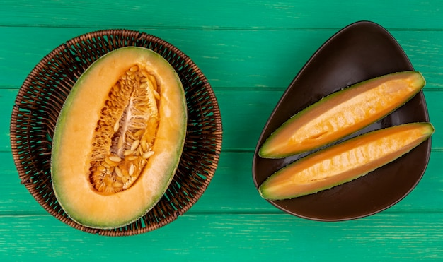 Top view of halved cantaloupe melon on a bucket with slices on a brown bowl on green surface