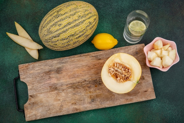 Top view of halved melon on a wooden kitchen board with slices of melon on a pink bowl on green surface