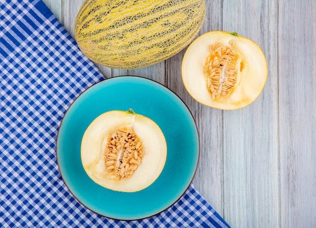 Top view of halved melons on a blue plate on blue checked tablecloth on grey wooden surface