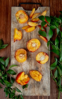 Top view of halves of fresh ripe peaches on a wooden cutting board with green leaves on rustic table