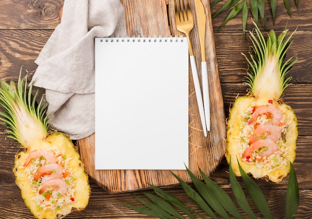 Top view halves of pineapple with copy space notepad
