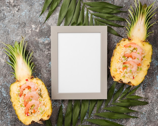 Top view halves of pineapple with empty frame