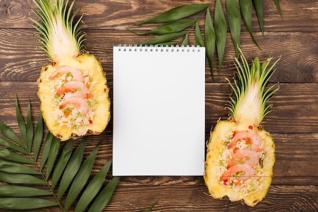 Top view halves of pineapple with notepad