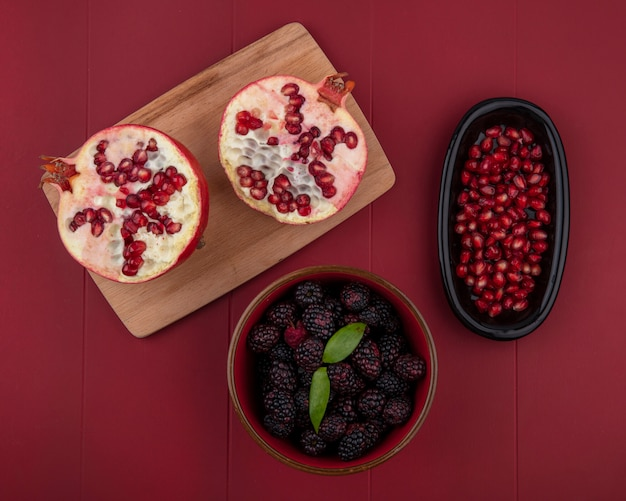 Top view of halves of pomegranate on a cutting board with blackberry on a red surface