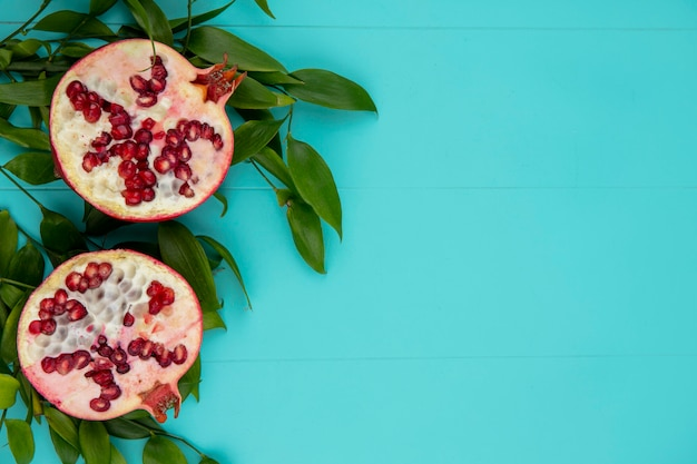 Top view of halves of pomegranate on leaf branches on a blue surface