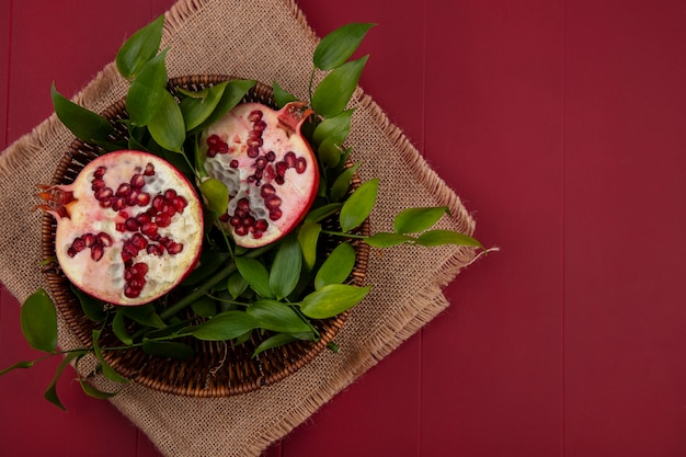 Top view of halves of pomegranate with leaf branches in a basket of beige napkin on a red surface