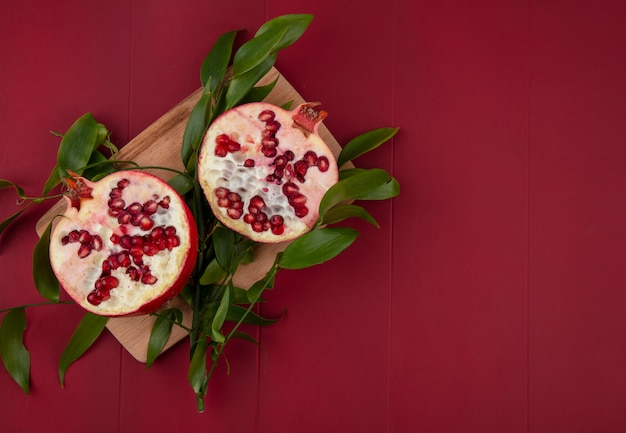 Top view of halves of pomegranate with leaf branches on a cutting board on a red surface