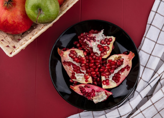 Top view of halves of pomegranates on a black plate with colored apples in a basket on a red surface