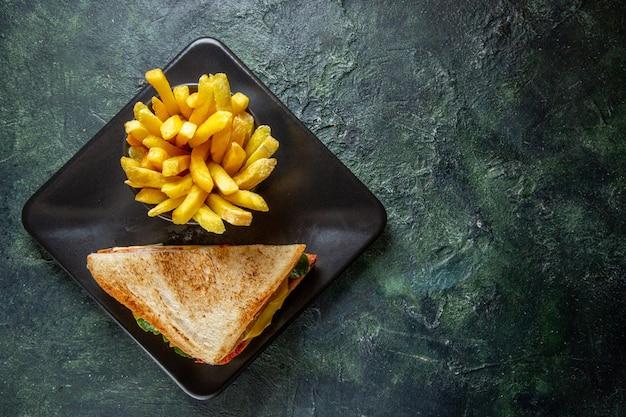 어두운 표면에 접시 안에 감자 튀김과 상위 뷰 햄 샌드위치