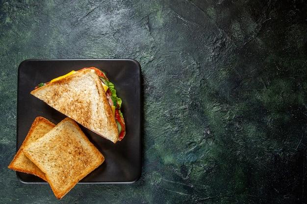 Вид сверху бутерброды с ветчиной с тостами внутри тарелки на темной поверхности