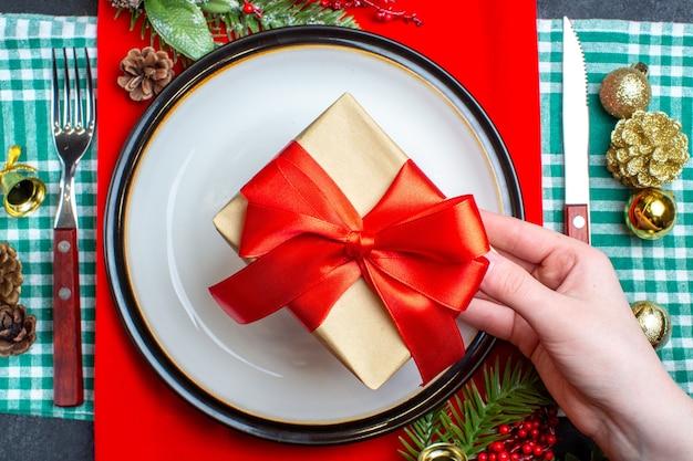 Vista dall'alto della mano che tiene una bella confezione regalo con nastro rosso a forma di fiocco su un piatto e set di posate accessori per la decorazione su asciugamano spogliato verde