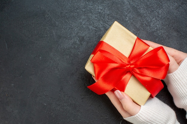Vista dall'alto della mano che tiene un bel regalo con nastro rosso a forma di fiocco sul lato su sfondo scuro