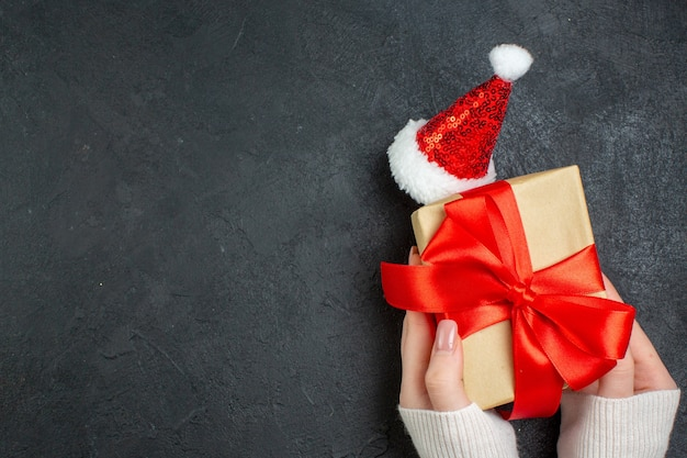 Top view of hand holding beautiful gift with bow-shaped ribbon next to santa claus hat on dark background