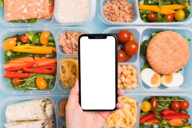 Top view hand holding blank phone over variety of lunchboxes