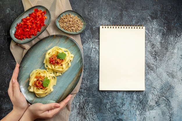 Top view of hand holding a blue plate with delicious pasta meal served with tomato and meat for dinner on tan color towel its ingredients next to spiral notebook