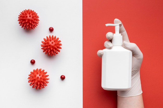 Top view of hand holding bottle of liquid soap with viruses