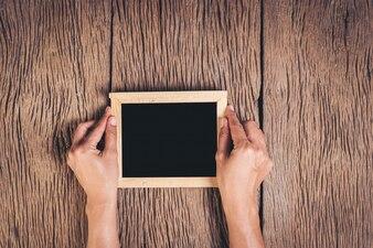 木材の背景に黒板を持っているトップビュー手