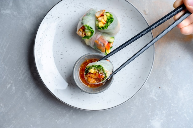Top view hand holding chopsticks with spring-roll and dip it in sweet and sour red sauce
