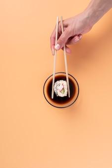 Вид сверху рука, держащая палочки для еды