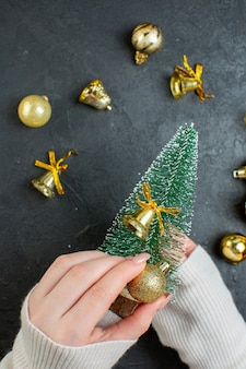 Top view of hand holding a christmas tree and decoration accessories on dark table