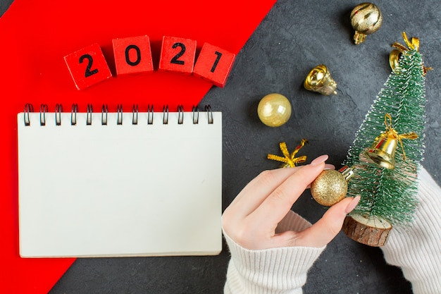 Top view of hand holding christmas tree and decoration accessories with numbers and notebook on dark table