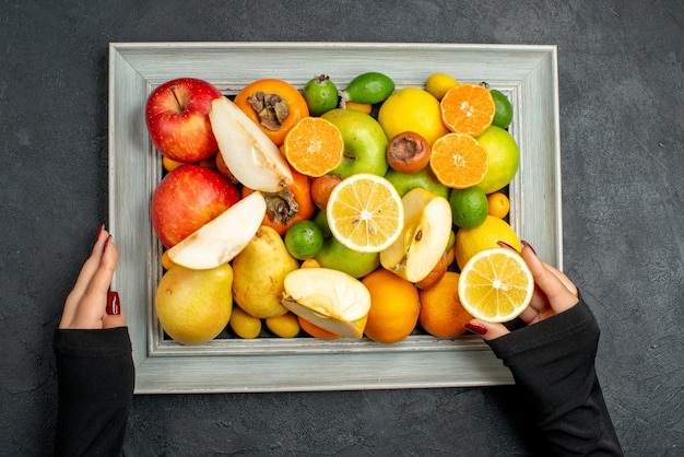 Top view of hand holding collection of whole and cut fresh fruits in picture frame on black table