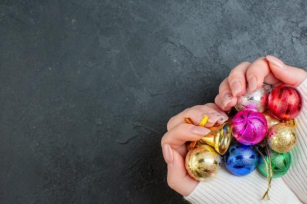 Vista dall'alto della mano che tiene gli accessori decorativi colorati su sfondo scuro