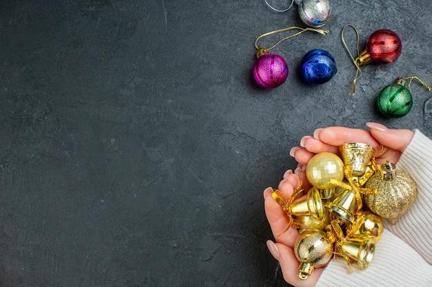 Vista superiore della mano che tiene gli accessori di decorazione colorati sul tavolo scuro