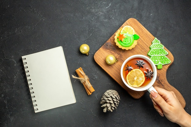 Top view of hand holding a cup of black tea xsmas accessories conifer cone and cinnamon limes on a wooden cutting board on black background