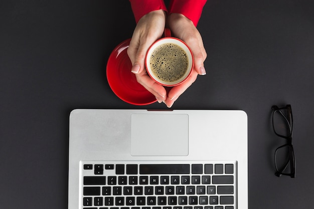 Top view of hand holding cup of coffee on desk with laptop