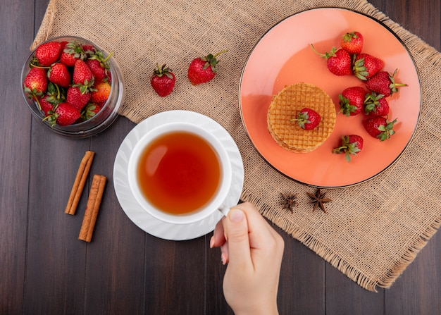 Top view of hand holding cup of tea and plate of waffle biscuits and bowl of strawberries on sackcloth with cinnamon on wooden surface