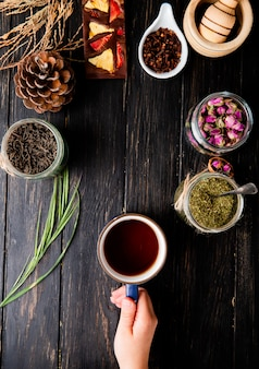 Top view of a hand holding a cup of tea and various spices and herbs on black wood with copy space